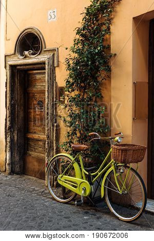 Old street in Trastevere in Rome, Italy, stylish bycice parked in front of shop entrance