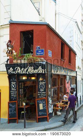PARIS , France- June 01, 2017: View of typical paris cafe in Paris. Montmartre area is among most popular destinations in Paris, Le Petit Moulin is a typical cafe.
