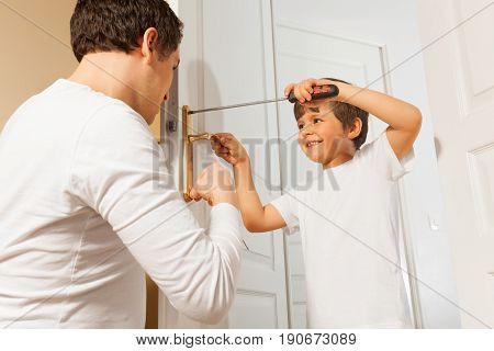 Portrait of six years old boy assembling door handle using a screwdriver under the supervision of his father