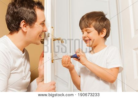 Close-up portrait of happy young father and his kid son repairing door handle at home together