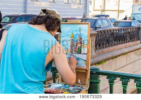 Saint-petersburg Russia - July 27 2016: The artist paints the temple of the Savior on the Blood