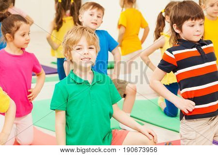 Portrait of happy six years old blond boy bending knee, practicing gymnastics in children's group