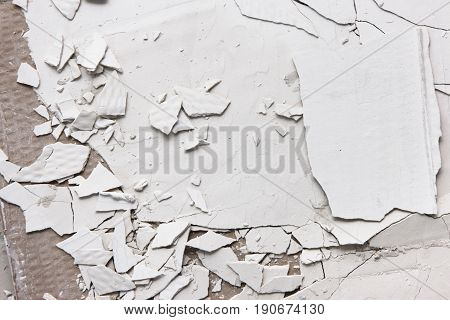 Pieces of white cracked plaster, closeup. Old peel wall background with free space. Repair and construction. Error in the technology of application of building materials