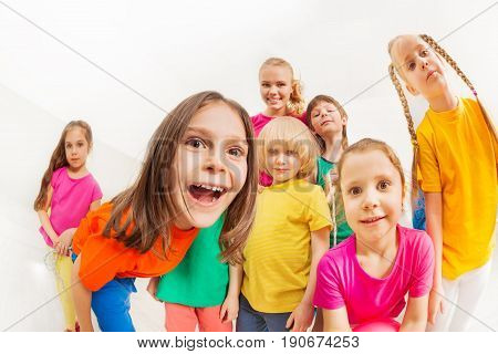Fish eye picture of children's sports team, 5-6 years old boys and girls, having fun with young female coach, standing together against blanked background