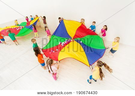 Top view picture of happy kids standing in a circle and playing parachute games in light gym