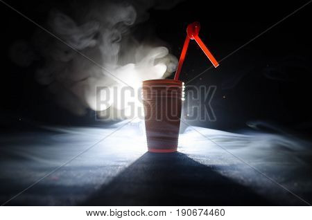 Stack Of Orange Plastic Cups With Straw On Dark Background