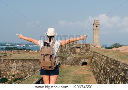 Girl Traveler With A Backpack. City Clock Tower In The Town Of Galle In Sri Lanka. Galle - The Large