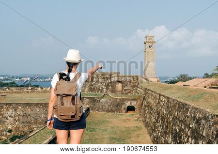 Girl traveler with a backpack. City clock tower in the town of Galle in Sri Lanka. Galle - the largest city and port in the south of Sri Lanka the capital of the southern province and a popular tourist destination