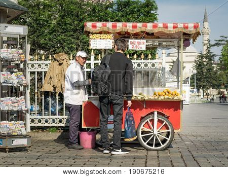 Istanbul Turkey - April 16 2017: Tourist buying fast food meal from a traditional Turkish chestnut and corn cart in Sultan Ahmed Square