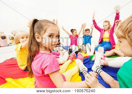 Portrait of beautiful preschool girl playing circle games, holding hands together with friends, sitting on rainbow parachute in gym