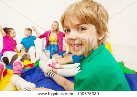 Close-up portrait of happy blond preschool boy playing circle games with friends and looking at camera