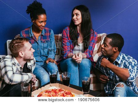 Four young interracial friends sit on couch at home with fresh pizza. Friendship, communication, fun and leisure , relationship, jealousy, gossip concept.