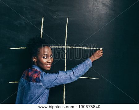 Game tic tac toe, happy afroamerican girl draw white lines to play on wall blackboard. Fun, leisure, joy and entertainment, strategy concept.