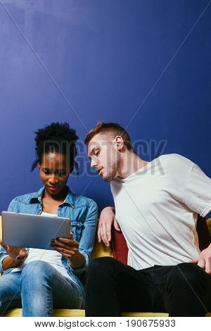Relationship problem in interracial couple, busy woman with tablet ignore man, she making business. Partner want attention, try to communicate.