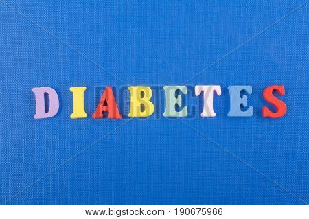DIABETETES word on blue background composed from colorful abc alphabet block wooden letters, copy space for ad text. Learning english concept