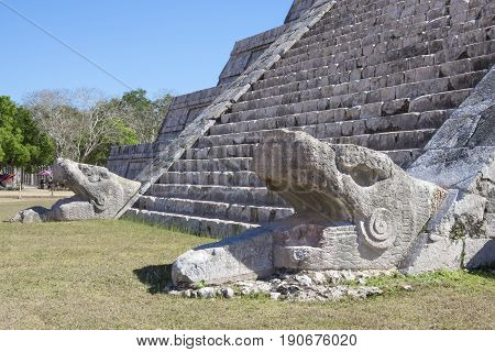 Two serpent heads at bottom of giant stairway leading up El Castillo pyramid on clear sunny day at Maya ruins of Chichen Itza in Yucatan Mexico