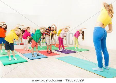 Female gymnastics coach teaching group of 5-6 years old kids making bending sideways in fitness class
