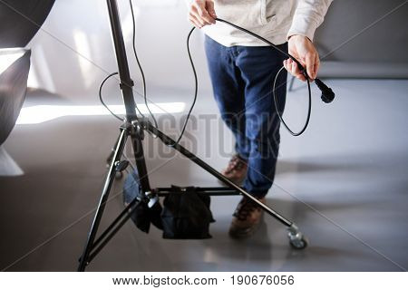 Assistant work with tripod in photostudio. Unrecognizable man setting the photo equipment. Professional photographer is adjusting studio for photographing.