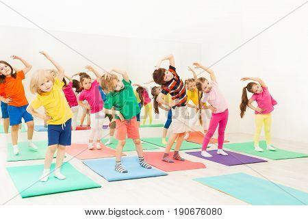 Group of happy kids, 5-6 years old girls and boys, doing side bending exercises in gym