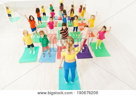 Big group of sporty kids doing gymnastic exercises with female instructor, holding their arms upwards, in fitness class