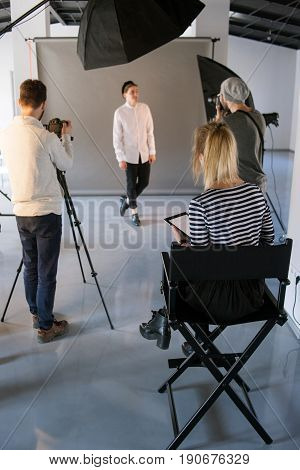 Art director looking over session. Big creative team working in studio. Photographer and videographer taking model shots while woman observing. Production of commercials backstage