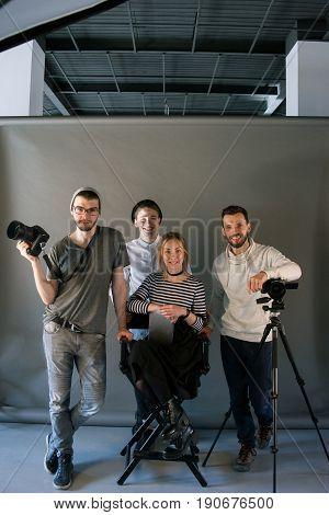 Production team posing in studio interior. Shot of art people looking at camera at the screen. End of hard work , photo for memory, friendship, crew concept