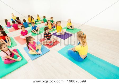 Group of sporty kids sitting on yoga mats and doing butterfly stretch with female instructor in exercise room