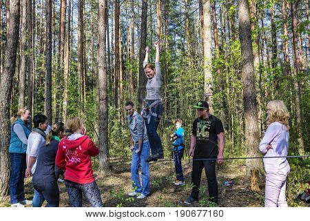 Belarus, Minsk - 05/13/2016: A woman trains to walk on a tight rope with insurance