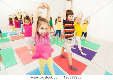 Group of sporty kids standing on mats with clasped hands overhead, stretching during gymnastic activity in gym