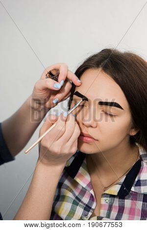Beautician is coloring with henna brow of young girl. Unrecognizable woman hand dying model's eyebrows.