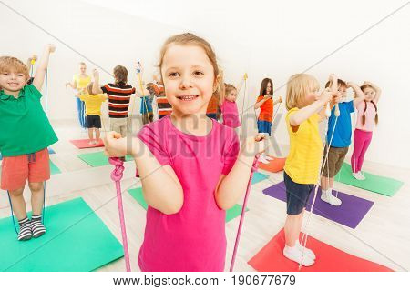 Group of happy 5-6 years old boys and girls having fun with jumping ropes in gym