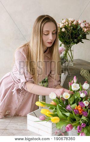 Florist choose flower for bouquet. Decorator workshop. Woman in flower shop , taking care about tulips assortment