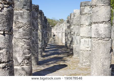 Vertical stone pillars casting shadows under sunny clear sky at the Court of the Thousand Columns at Chichen Itza in Yucatan Mexico