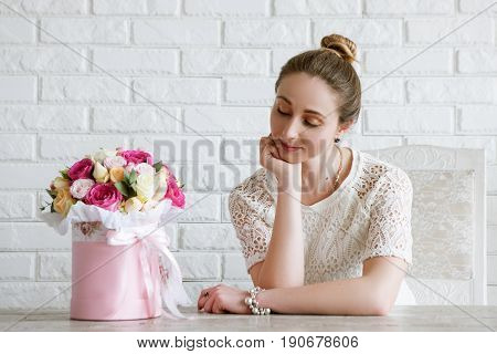 Daydreaming woman with gift. Luxury flower bouquet. Colorful roses boxing in pink box in the shape of a cylinder. Beautiful and sensual present for March 8, Valentine's Day