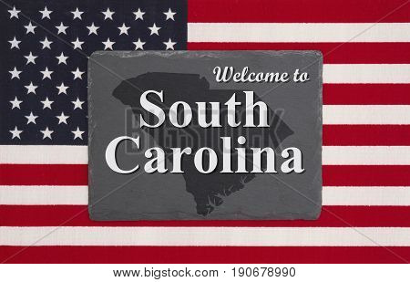 Welcome to South Carolina with state map on a black chalkboard on a United States of America flag