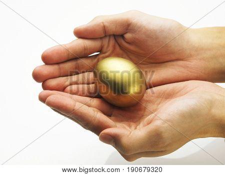 Pair of hand holding the golden egg