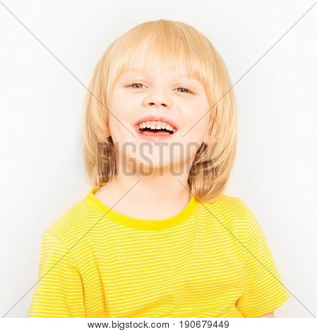 Portrait of joyful five years old blond boy looking at camera standing against white background