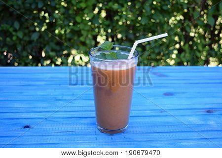 glass of apple, peach smoothie with straw on wooden table. Protein cocktail. Healthy drink. Fresh homemade smoothie. Healthy breakfast of smoothie