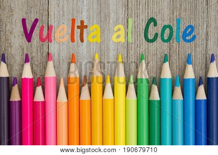 Back to School in Spanish Vuelta al Cole text with colorful pencil crayons on a weathered wood