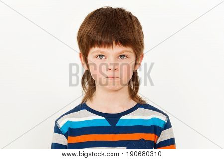 Portrait of angry seven years old boy with pursed lips, standing against white background