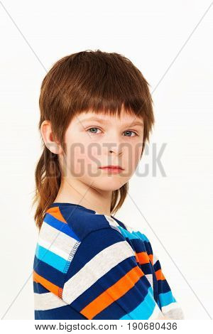 Side view portrait of Caucasian seven years old boy looking at camera, isolated on white