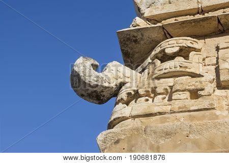 Closeup low angle stone sculpture of rain god Chaac on corner of temple building at Chichen Itza on clear sunny day in Yucatan Mexico