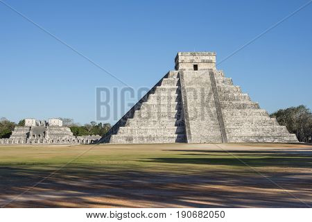 Famous el Castillo Temple of Kukulkan and Temple of the Warriors at Maya ruins of Chichen Itza during late afternoon with clear blue sky shadows and no people