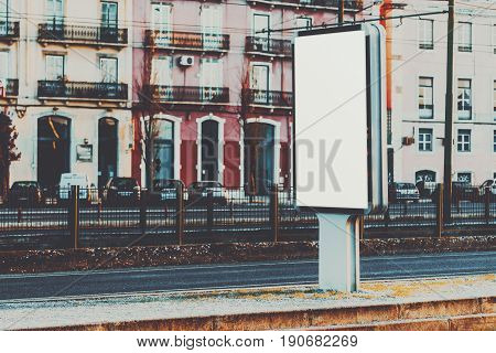 Vertical information banner mock-up near railroad and highway blank information placeholder in evening urban settings white empty city billboard with copy space for logo your text or advertising