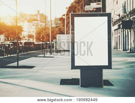 Vertical mock-up of city poster with thick edges blank white billboard in urban settings empty street information placeholder on sidewalk with copy space for logo advertising or your messages