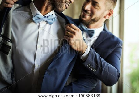 Closeup of gay couple helping each other dress up