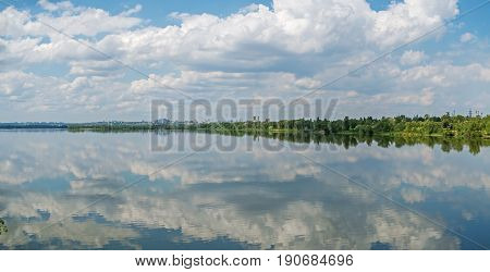 A picturesque panoramic view of the city outskirts on river side against a cloudy sky