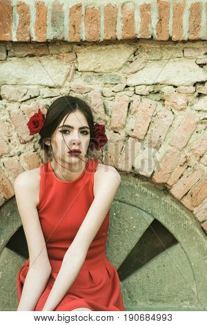 flamenco girl or spanish woman with fashionable makeup and rose flower in hair happy girl in red dress on stony wall background beauty and fashion