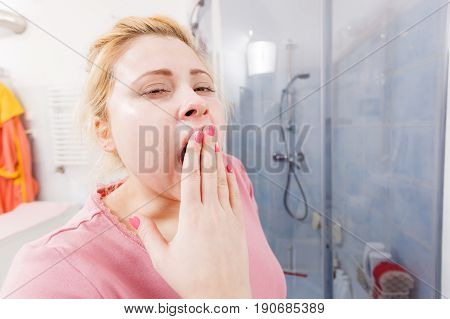 Closeup Of Sleepy Blonde Woman In Bathroom