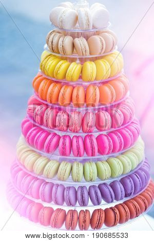 Colorful french macarons multilevel cake pyramid on plastic dessert stand or plate on blurred background. Food dieting. Birthday anniversary wedding celebration